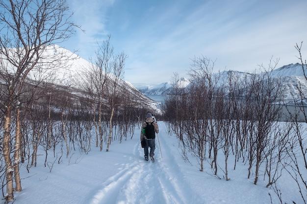 Viajante em grupo caminhando em uma colina de neve com céu azul ensolarado na ilha de senja, noruega