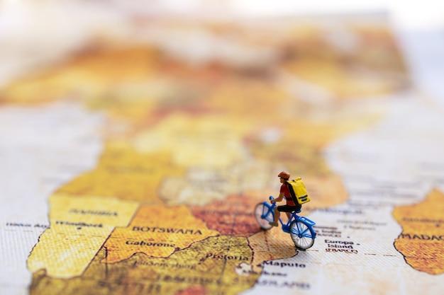 Viajante em miniatura com uma mochila, pedalando no mapa-múndi vintage.