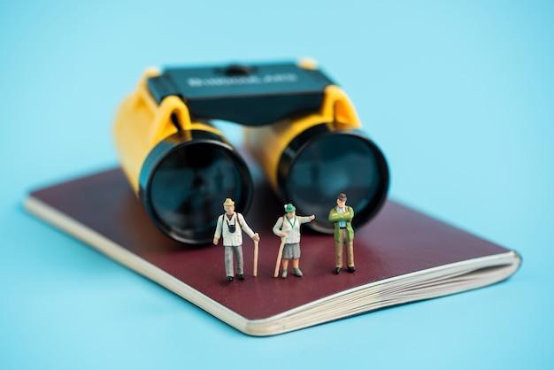 Viajante em miniatura e binóculos no livro de passaporte