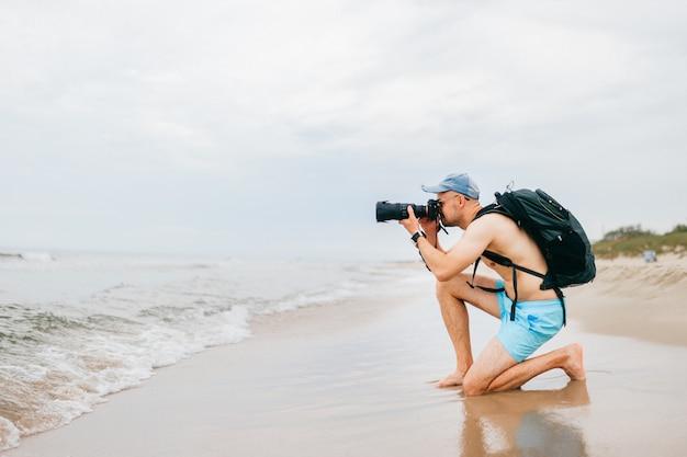 Viajante em topless com câmera fotográfica tirando foto do mar.