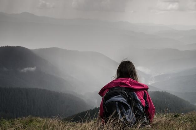 Viajante em uma viagem de trekking para montanhas repousa na área de montanha e olha a forte chuva de trovões caindo nas proximidades