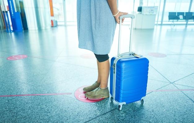 Viajante esperando no aeroporto mantendo o distanciamento social. distância social para evitar covid 19.