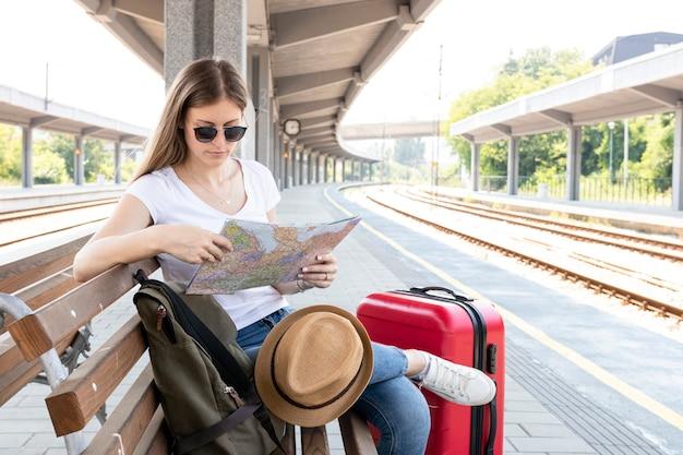 Viajante esperando o trem e olhando o mapa