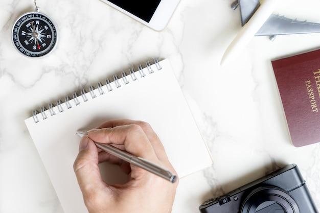 Viajante está escrevendo na página do diário em branco com caneta de metal