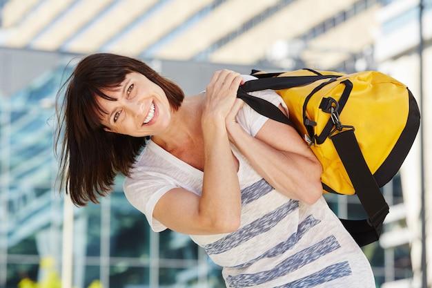 Viajante feliz carregando mochila por cima do ombro