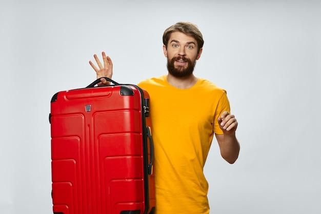 Viajante feliz com uma mala vermelha e uma camiseta amarela