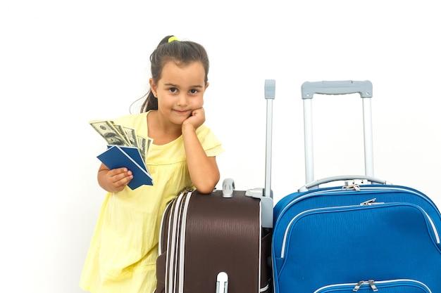 Viajante feliz da criança que mostra o passaporte com a bagagem isolada no conceito branco, do curso e das férias