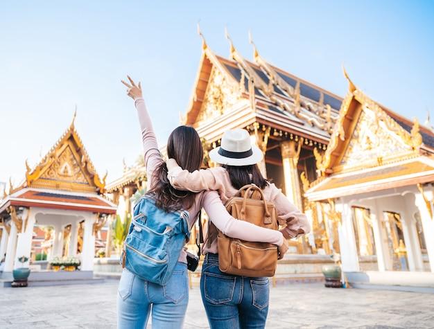 Viajante feliz de duas mulheres no templo na tailândia