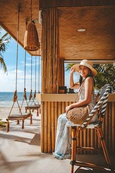 Viajante feliz mulher asiática com chapéu e vestido relaxando em balanço no café da praia, koh chang, tailândia
