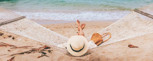 Viajante feliz mulher asiática com chapéu relaxando em uma rede na praia em koh chang, trad, tailândia
