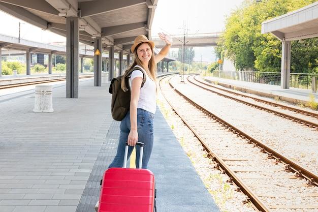Viajante feliz sorrindo na estação de trem
