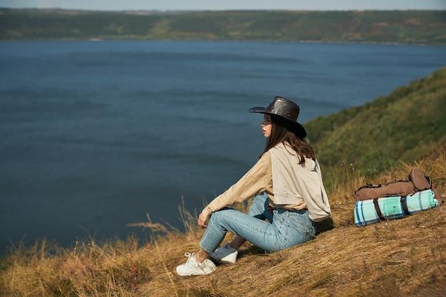 Viajante feminino atraente com mochila sentado na colina alta e olhando para o rio dniester. conceito de estilo de vida ativo e beleza da natureza.