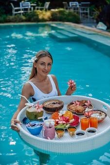 Viajante feminino atraente em poses de maiô na piscina, olhando para a câmera com mesa flutuante cheia de alimentos exóticos.