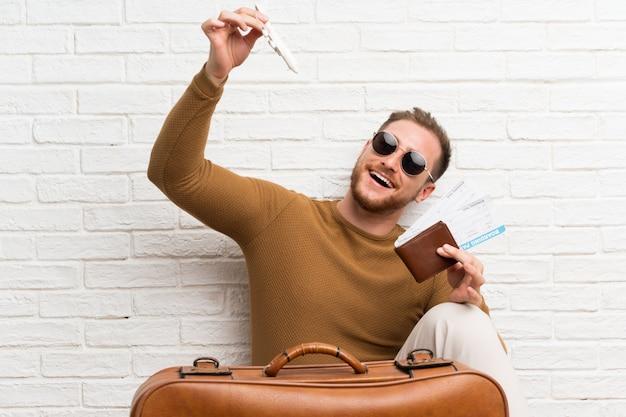 Viajante homem com mala e cartão de embarque e segurando um avião de brinquedo