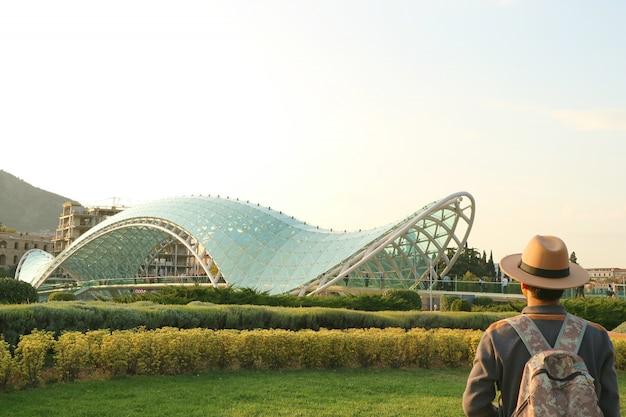 Viajante impressionado com a ponte da paz, um marco icônico de tbilisi, geórgia