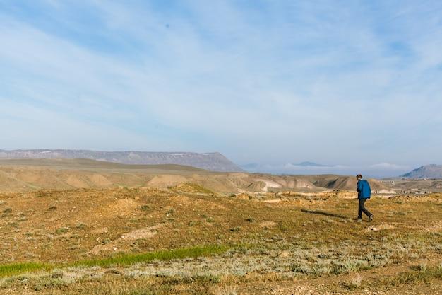 Viajante individual caminha ao longo de um vale na montanha vista traseira do homem com uma mochila copie o espaço