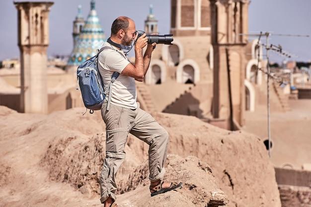 Viajante individual tira foto em uma cidade velha durante uma viagem individual independente, kashan, irã