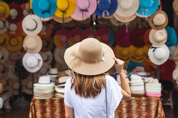 Viajante jovem à procura de chapéu no mercado local na tailândia