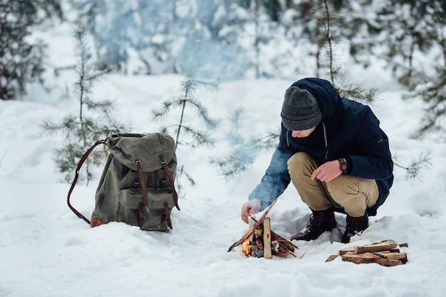 Viajante jovem acende um fogo que esquenta na floresta de inverno