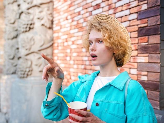Viajante jovem alegre ruiva encaracolada segurando uma xícara de café e surpreso com os pontos turísticos