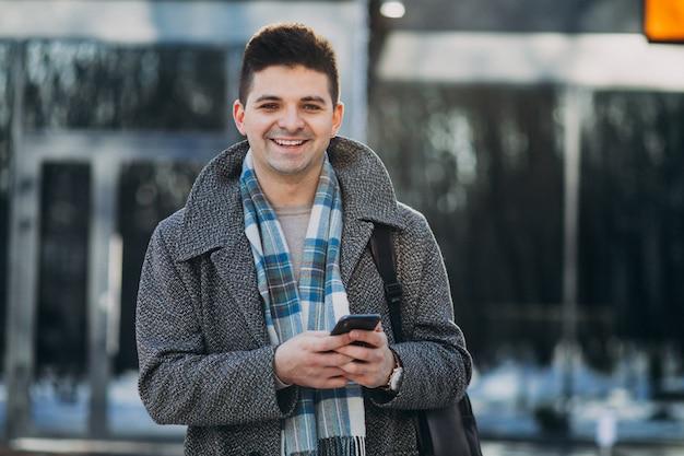 Viajante jovem bonito usando telefone fora