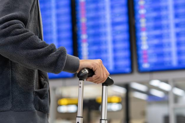 Viajante jovem com bagagem olhando para a placa de informação de voo no aeroporto internacional