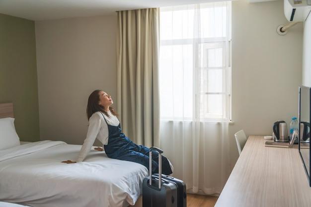 Viajante jovem com bagagem sentado na cama no quarto de hotel