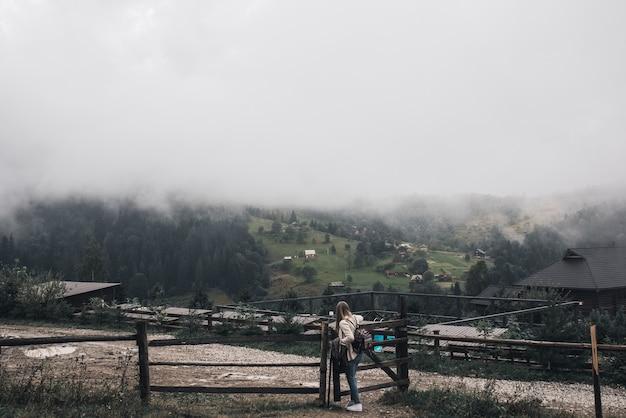 Viajante jovem e magra perto de uma cerca velha contra o fundo das altas montanhas dos cárpatos no nevoeiro