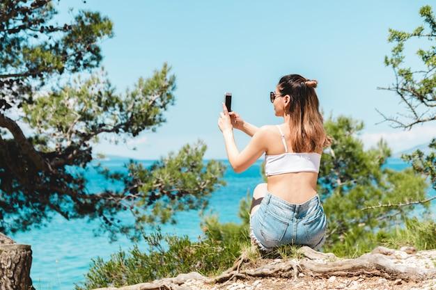 Viajante jovem em óculos de sol, tirando foto do cenário do mar em meio dia. mar azul e pinheiros