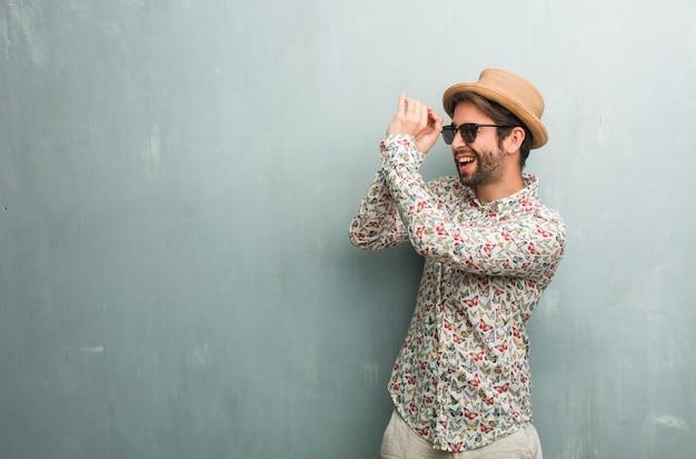 Viajante jovem homem vestindo uma camisa colorida, olhando através de uma lacuna, escondendo e squinting