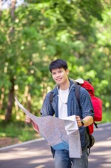 Viajante jovem mochileiro com mapa, ele carrega uma grande mochila durante o relaxamento ao ar livre nas férias de verão no teste da floresta, copie o espaço