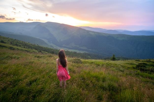 Viajante jovem mulher feliz em um vestido vermelho de pé na encosta gramada em uma noite de vento nas montanhas de verão, apreciando a vista da natureza ao pôr do sol.