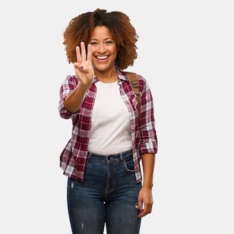 Viajante jovem negra mostrando o número três