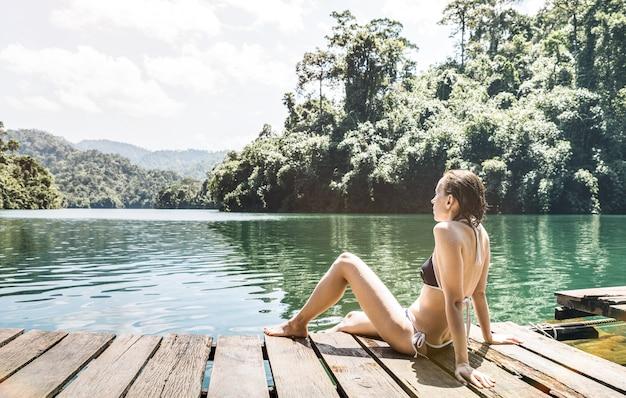 Viajante jovem no cais de madeira doca no lago cheow lan no parque nacional khao sok