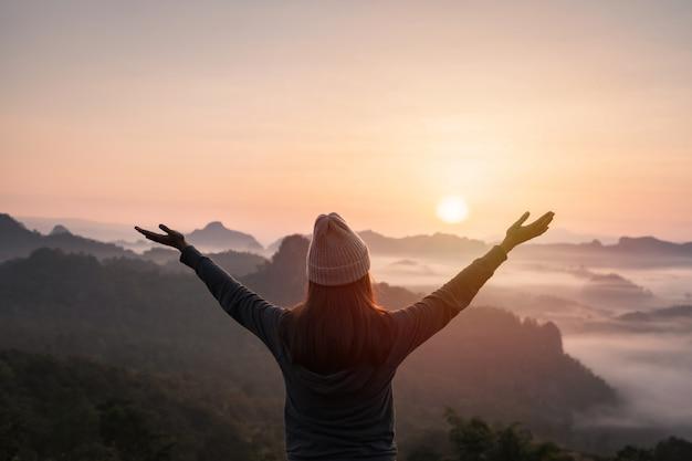 Viajante jovem olhando para o mar de névoa e pôr do sol sobre a montanha