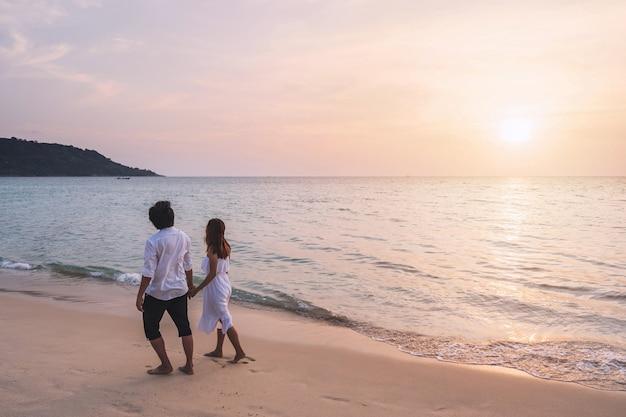 Viajante jovem segurando a mão do homem e olhando o belo pôr do sol na praia