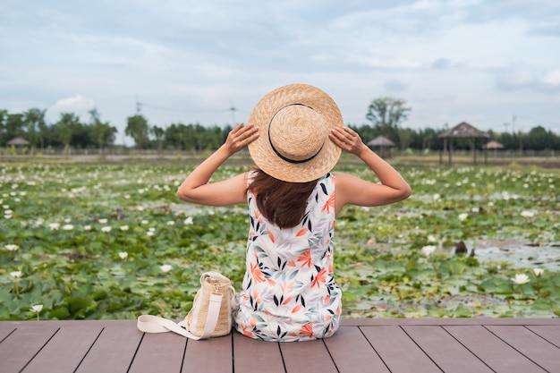 Viajante jovem sentado e olhando a lagoa de lótus