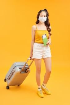 Viajante jovem usando máscara facial com mala mala em fundo laranja. conceito de viagem durante o coronavírus.