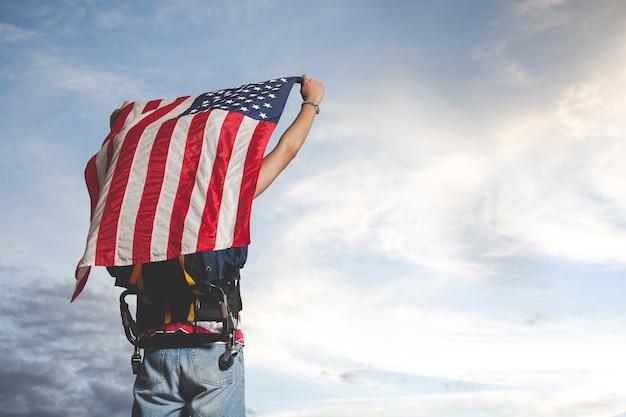 Viajante levantando uma bandeira na frente da vista do céu