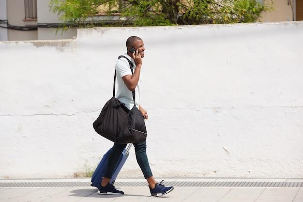 Viajante masculino americano africano andando lá fora e falando no celular