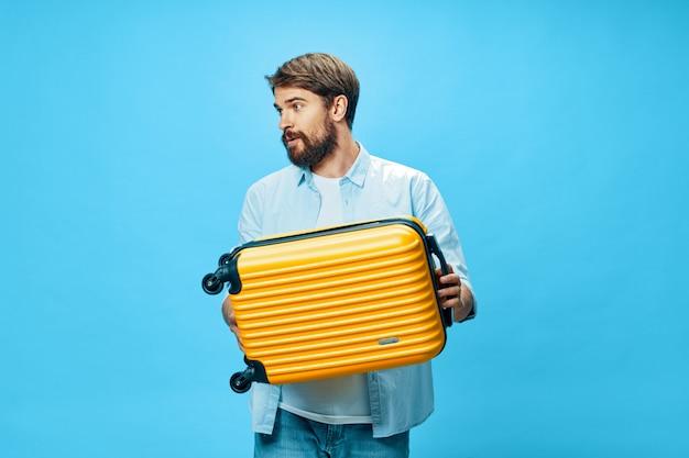 Viajante masculino com uma mala nas mãos posando no estúdio, férias