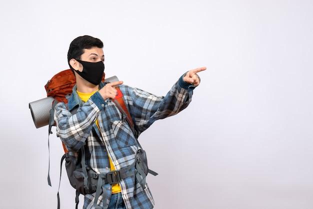 Viajante masculino de vista frontal com mochila e máscara apontando para algo