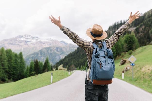 Viajante masculino feliz posando com as mãos ao alto em pé na estrada e olhando para árvores distantes
