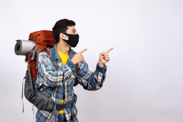Viajante masculino interessado de vista frontal com mochila e máscara apontando para algo