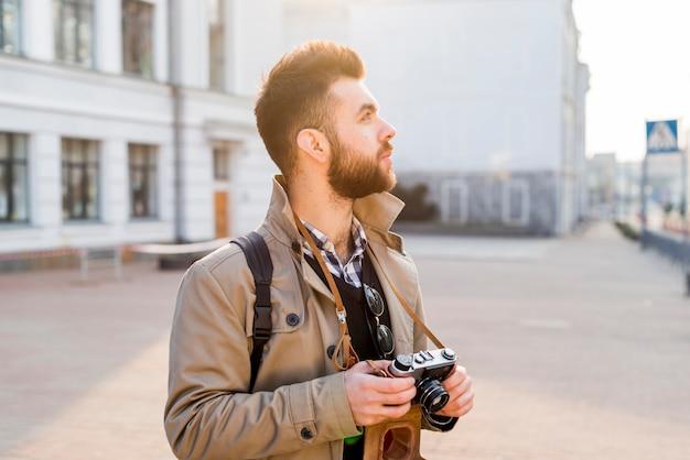 Viajante masculino segurando a câmera vintage na mão, olhando para os lugares da cidade