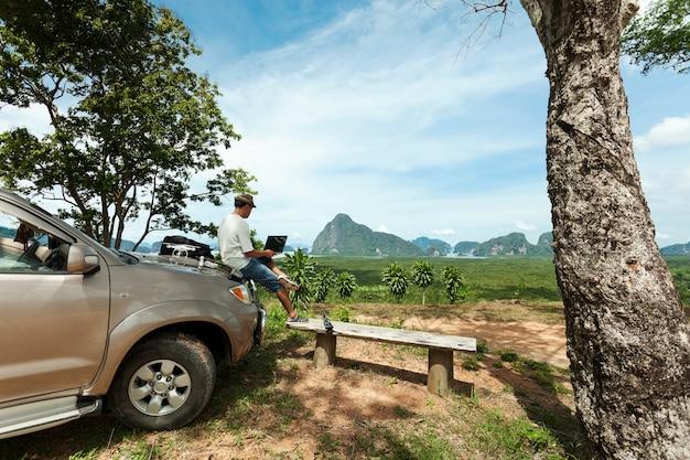Viajante masculino sentado em um capô de carro