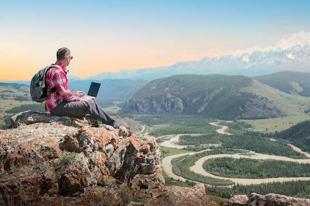 Viajante masculino trabalhar remoto no computador netbook e apreciando a paisagem de natureza de montanhas ao pôr do sol.