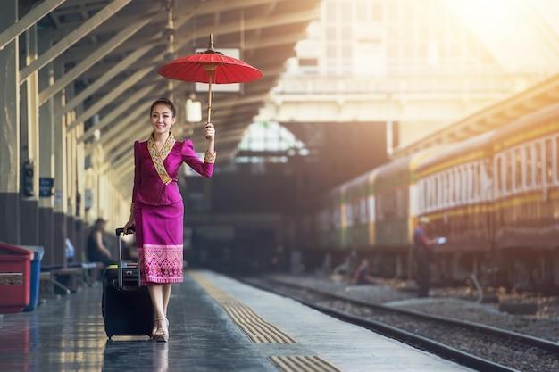 Viajante menina andando e espera o trem na plataforma ferroviária