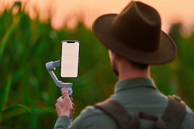 Viajante, mochileiro, blogueiro, com gimbal eletrônico de estabilizador de telefone manual e maquete de tela em branco tira uma selfie e grava um videoblog ao ar livre