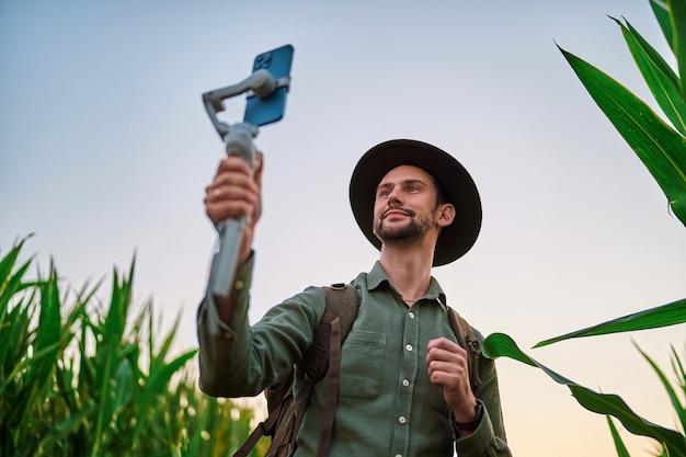 Viajante, mochileiro blogueiro, usando chapéu de feltro com gimbal eletrônico manual estabilizador de telefone tira uma selfie e grava videoblog ao ar livre